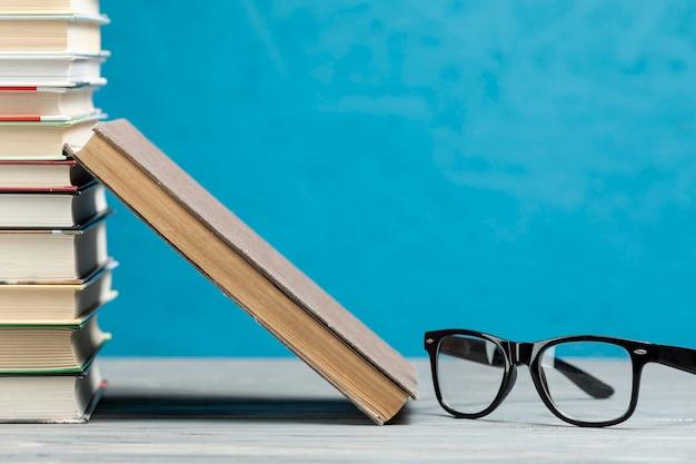 Pila di libri con gli occhiali vista frontale