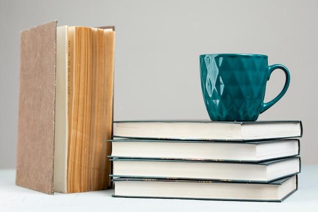 Pila di libri di vista frontale con una tazza