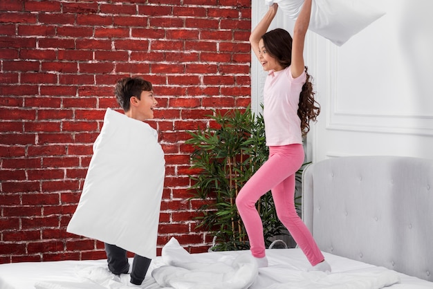 Front view pillow fights between siblings