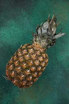 Vista frontale dell'ananas sulla superficie verde