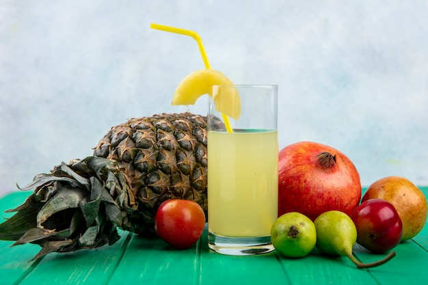Front view of pineapple juice with pineapple plum pomegranate peach apple on green surface and white surface
