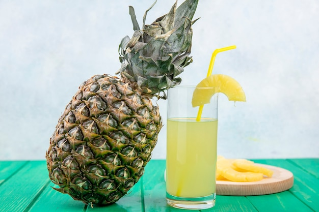 Front view of pineapple juice with pineapple slices on cutting board and pineapple on green surface and white surface