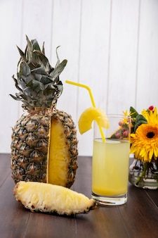 Front view of pineapple and pineapple slice and juice in glass with drinking tube and flowers on wooden surface