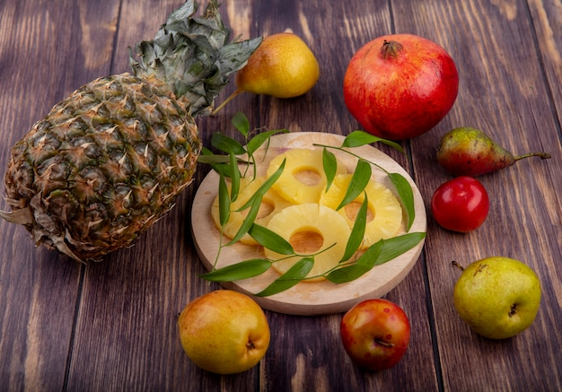 Front view of pineapple slices with leaves on cutting board and pineapple pomegranate apple peach plum on wooden surface