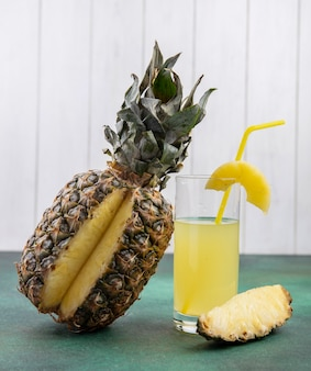 Front view of pineapple with one piece cut out from whole fruit and pineapple juice on green surface and white surface