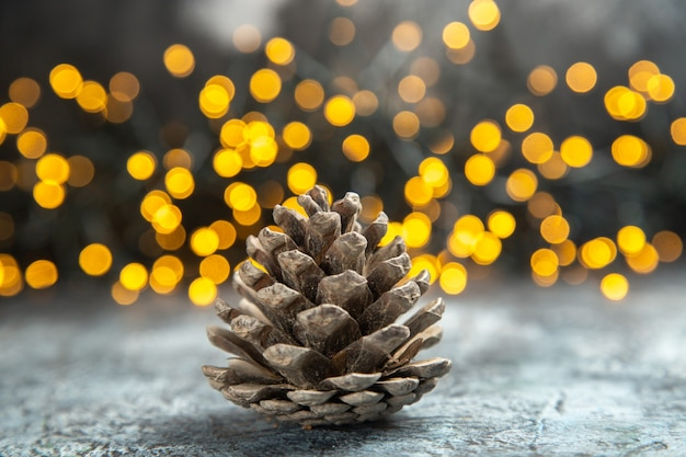 Front view pinecone on dark isolated surface xmas lights copy space