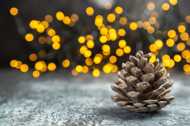 Front view pinecone on dark isolated surface xmas lights