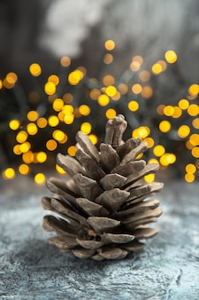 暗い孤立した表面のクリスマスライトの正面図の松ぼっくり
