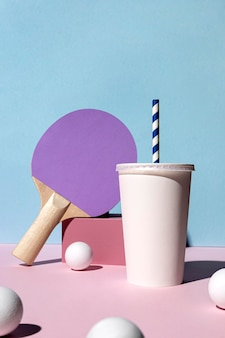 Front view of ping pong balls and paddle and paper cup