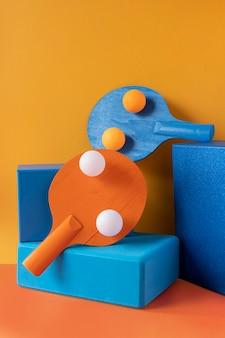 Vista frontale di palline da ping pong e pagaie su forme di piedistallo