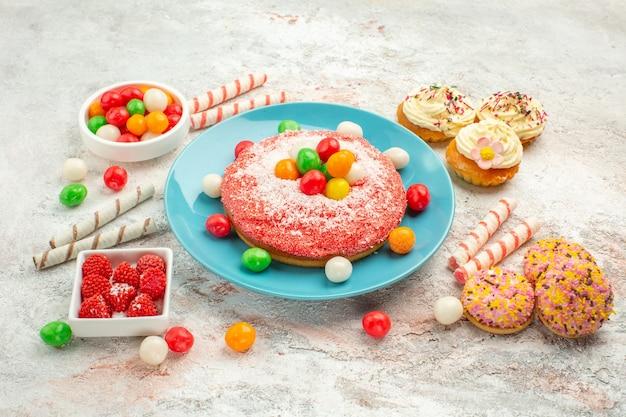 白い背景の上のカラフルなキャンディーと正面図ピンクのケーキグッディレインボーキャンディーデザートカラーケーキ