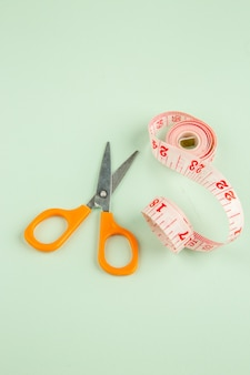 Front view pink centimeter with scissors on green surface sewing photo clothes pin sew color
