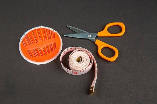 Вид спереди розовые сантиметры с ножницами и иголками на темной поверхности темная булавка шитье цвет мера фото