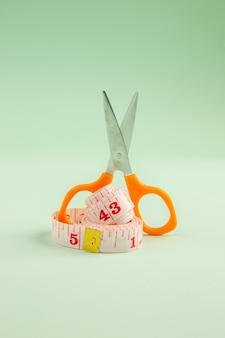 正面図緑の表面にハサミでピンクのセンチメートル服写真縫製縫製カラーピン針