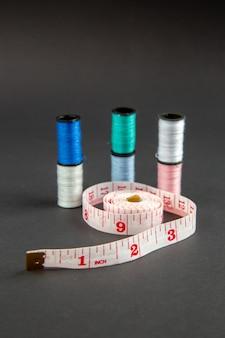 Вид спереди розовые сантиметры с нитками на темной поверхности темнота булавка мера фото цвет