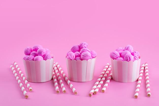 Una vista frontale rosa, biscotti deliziosi e gustosi insieme a caramelle in stick sul rosa, zucchero candito biscotto biscotto