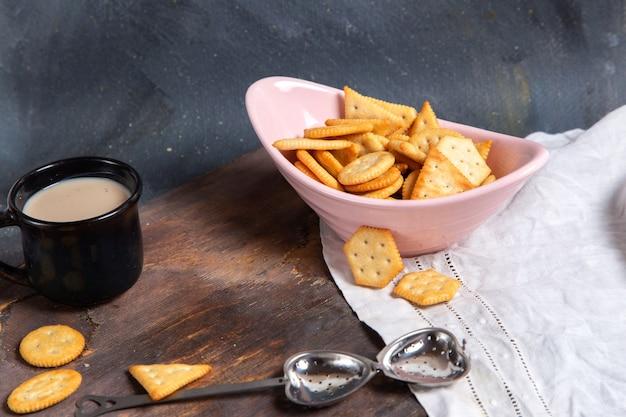 灰色のミルクのカップとクリスプの完全正面ピンクプレート