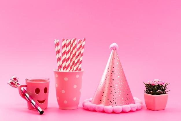 Una vista frontale rosa, -bianco, caramelle stick con divertente tazza di compleanno berretto e piccola pianta su rosa, caramelle di colore