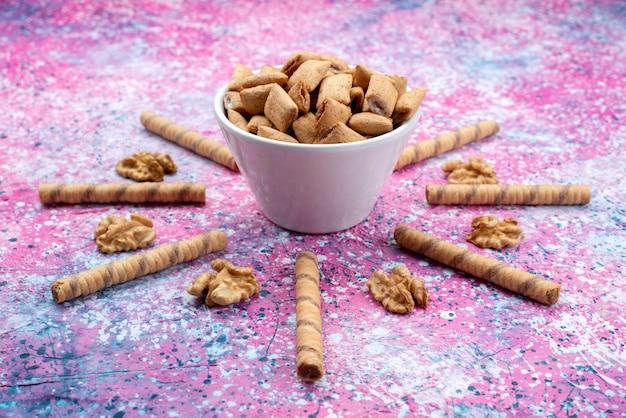 Печенье из трубочки, вид спереди, с крекерами-подушками внутри тарелки на цветном сахарном сладком крекере