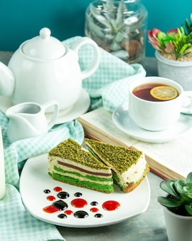Front view pistachio cake with a cup of tea and a slice of lemon