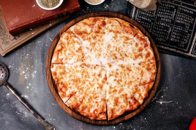갈색 둥근 나무 책상과 어두운 표면에 치즈와 전면보기 피자