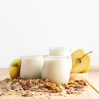 Вид спереди простого йогурта в баночках с овсом и фруктами