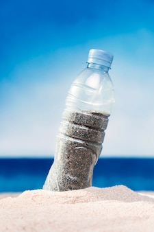 Front view of plastic bottle filled with sand on beach