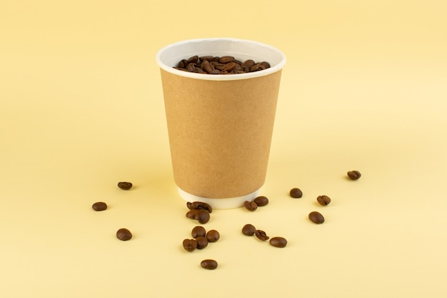 A front view plastic coffee cup with brown coffee seeds on the yellow wall