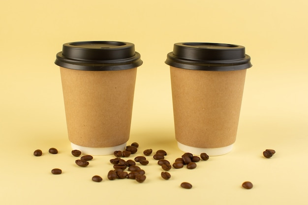 A front view plastic coffee cups delivery coffee pair with brown coffee seeds on the yellow surface