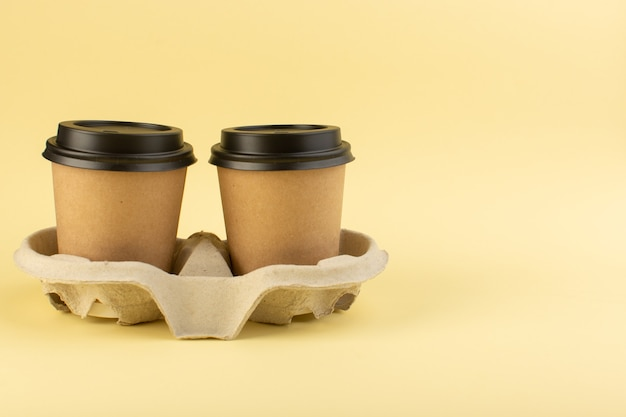 A front view plastic coffee cups delivery coffee pair on the yellow wall