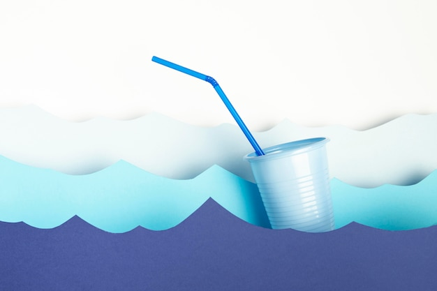 Front view of plastic cup with straw and paper waves