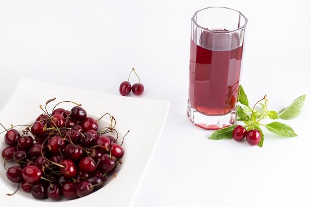 Тарелка переднего вида с вишней кислой и мягкой вместе с листьями вишневого сока на белом