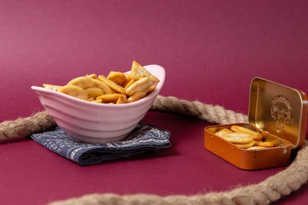 Piatto di vista frontale con cracker rosa piatto con corde su viola