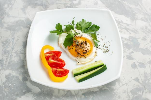밝은 흰색 책상에 음식 야채와 채소가있는 전면보기 플레이트
