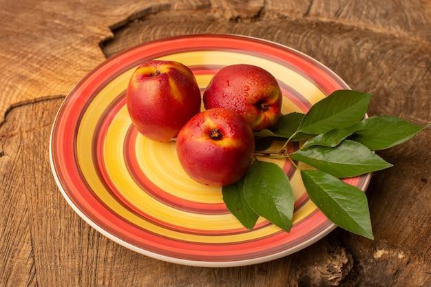 Тарелка переднего вида с персиками внутри красочной тарелки на деревянном столе