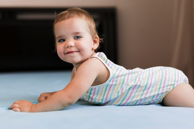 Front view of playful baby in bed