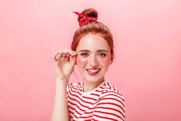 Vista frontale della giocosa ragazza allo zenzero con bende sugli occhi. studio shot di giovane donna facendo un trattamento di cura della pelle con il sorriso.