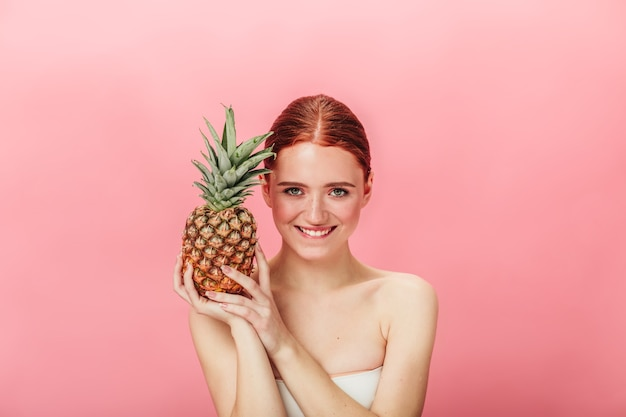 Front view of pleasant girl with exotic fruit. studio shot of ginger young woman with pineapple isolated on pink background.