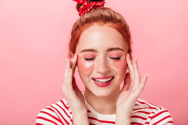 Vista frontale della ragazza caucasica soddisfatta con bende sugli occhi. studio shot di donna sorridente in maglietta a righe facendo un trattamento per la cura della pelle.