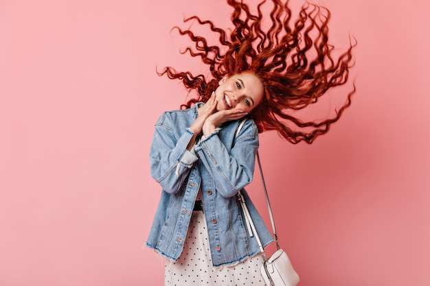 Front view of pleased ginger girl in casual attire. studio shot of red-haired woman in denim jacket dancing on pink background.
