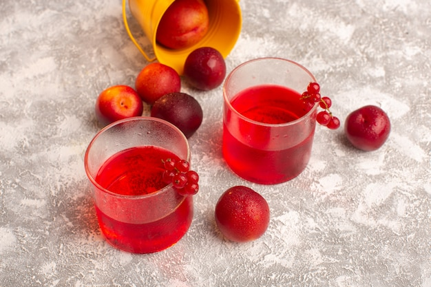 Vista frontale del succo di prugna rosso colorato con prugne fresche su grigio
