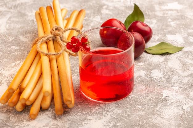Vista frontale di succo di prugna rosso colorato con prugne fresche e cracker stick su grigio