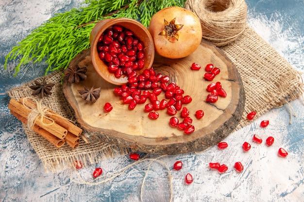 Гранат, вид спереди, разбросанные семена граната в миске на дереве, деревянная доска, соломенная нить, семена аниса корицы на сине-белом фоне
