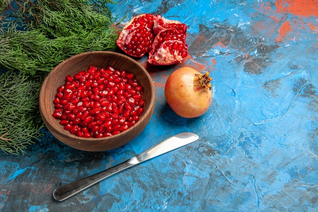 Front view pomegranate seeds in bowl dinner knife a cut pomegranate on blue background free space