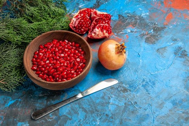 ボウルディナーナイフの正面図ザクロの種子青い背景の空きスペースにカットザクロ