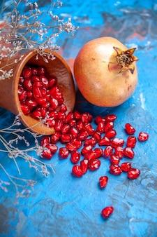 Вид спереди семена граната в деревянной миске и ветка сушеного полевого цветка граната на синем фоне