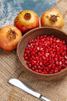 파란색 흰색 배경에 나무 그릇 저녁 식사 칼 석류에 전면 보기 석류 씨앗