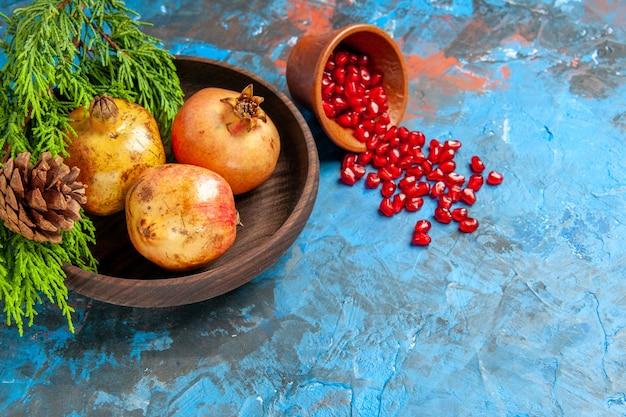 Семена граната, вид спереди, помещенные в деревянную чашку с разбросанными семенами граната на деревянной тарелке, ветка сосны на синем фоне, свободное пространство