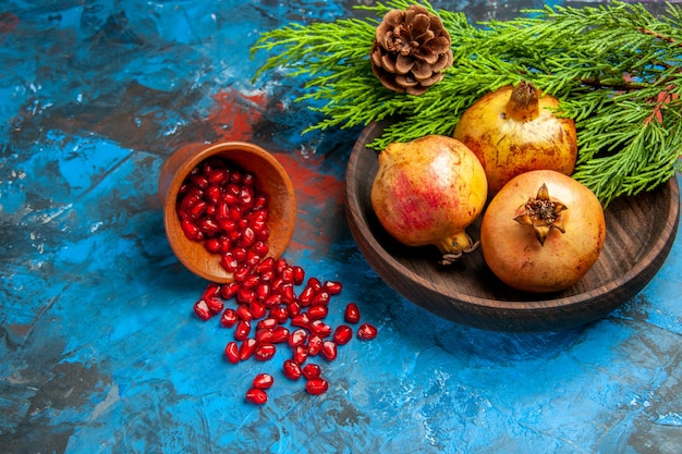 Front view pomegranate seeds placed in wooden cup with scattered seeds pomegranates on wooden plate on blue