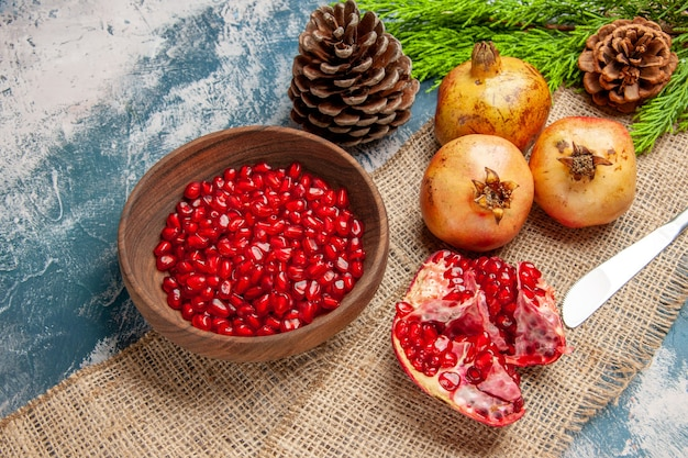 Front view pomegranate seeds in wooden bowl dinner knife pomegranates pine tree branch on blue-white background